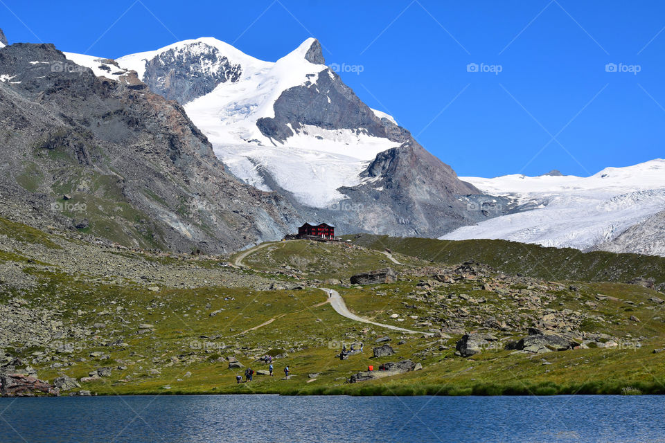 Swiss alps with a red house on a foothill