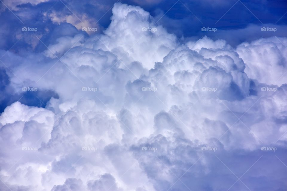 aerial view on fluffy clouds on the blue sky from plane window