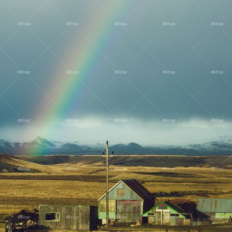 Rainbow over expansive landscape in Iceland. Beautiful rainbow over mountains and barn in Iceland