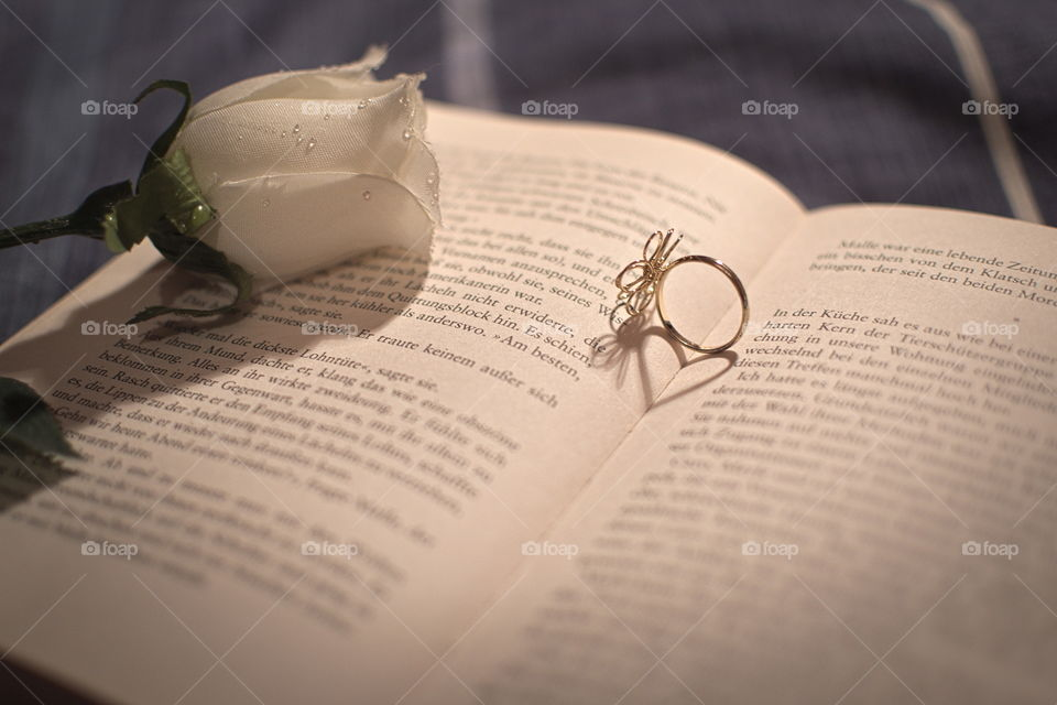 Open book with a white rose and a ring ot top, the ring forms a heartshaped shadow