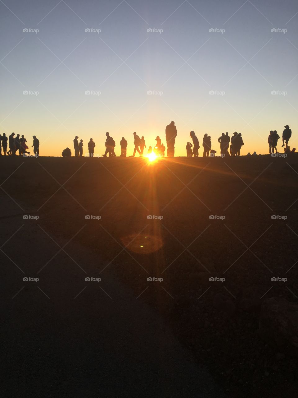 A group of people stand along a mountain ledge, silhouetted by the sunset.