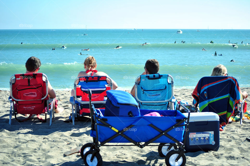 Four friends in beach chair chilling in ocean front during summer