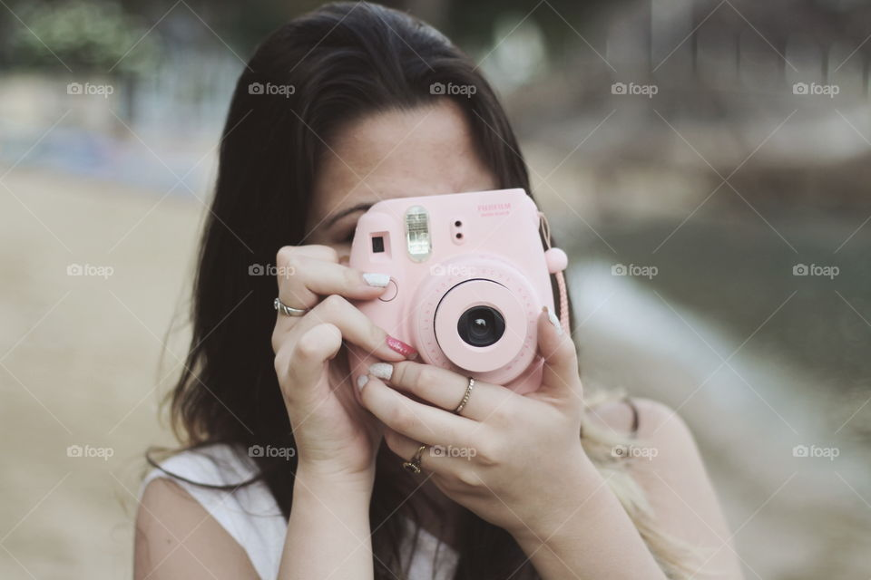 Girl taking a picture using a Polaroid camera