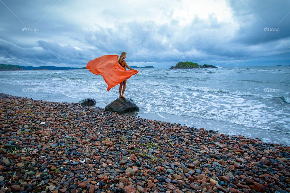 Young woman on the beautiful sea coast. Beautiful landscape, seascape.