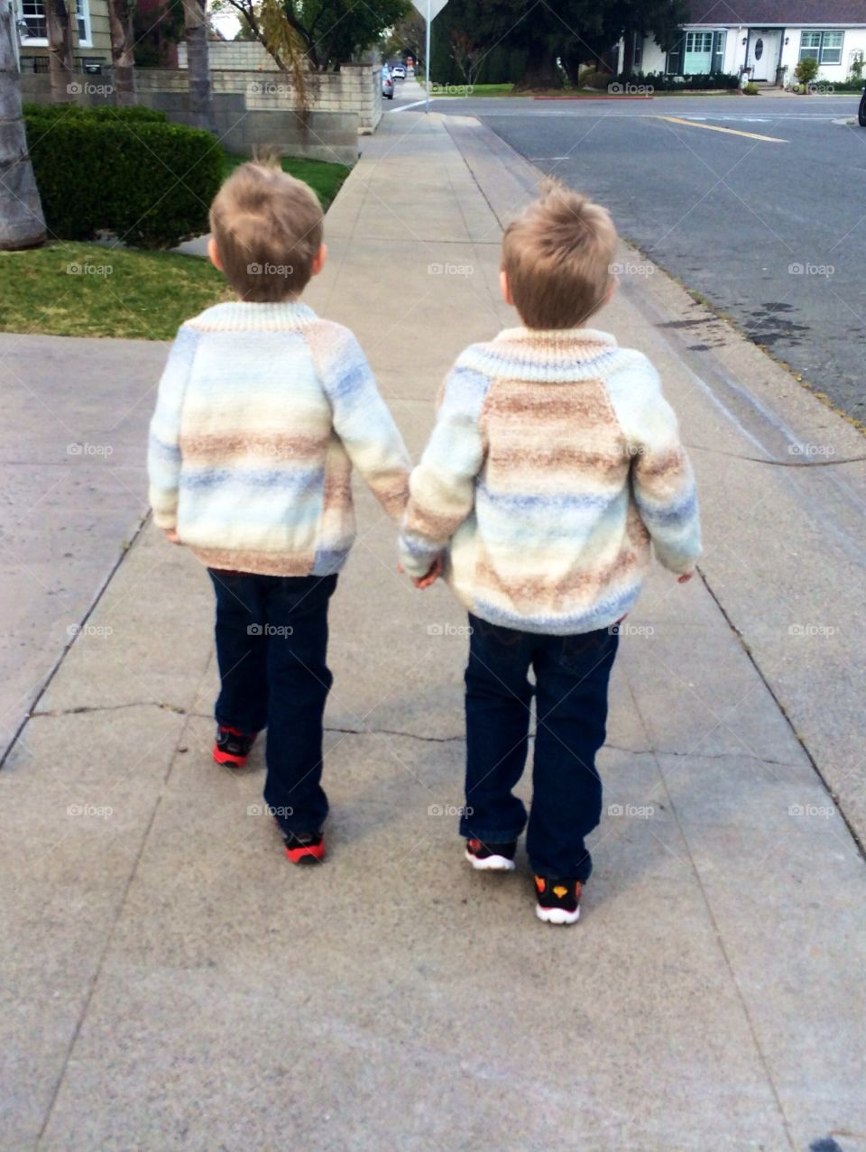 Brothers forever. Twin brothers holding hands during a walk