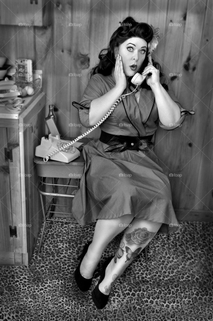 Surprise woman using retro telephone