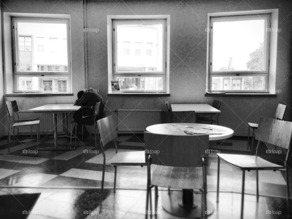 A long journey's day. Tired passenger sleeping at the table of bus station's cafeteria.