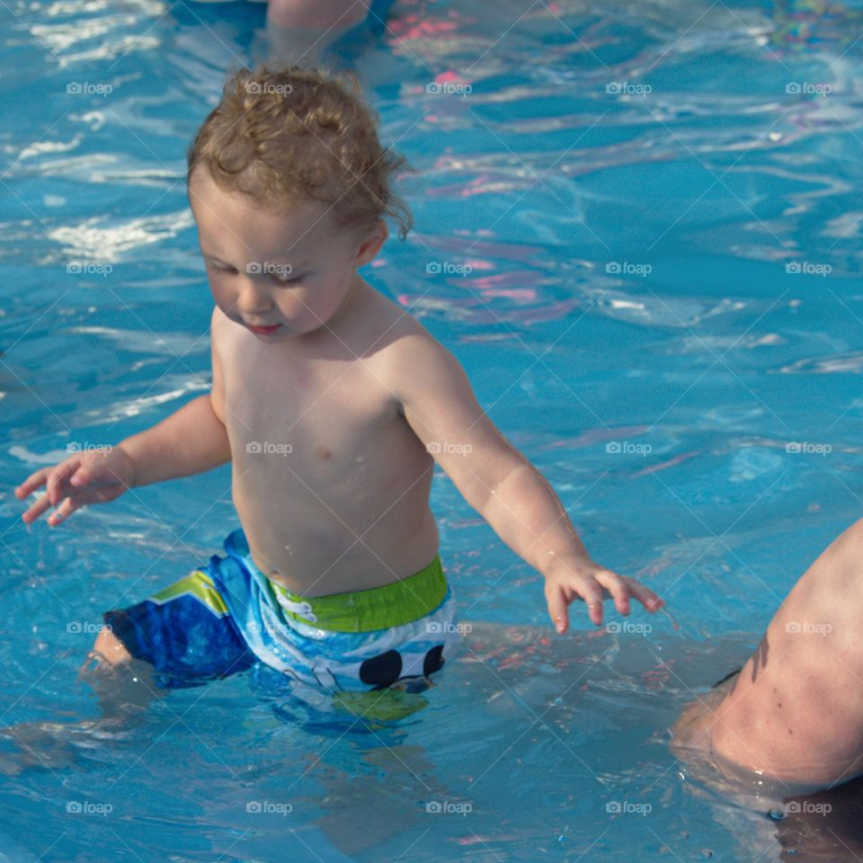 A toddler boy at the outdoor swimming pool for his first round of swimming lessons on a sunny summer evening.