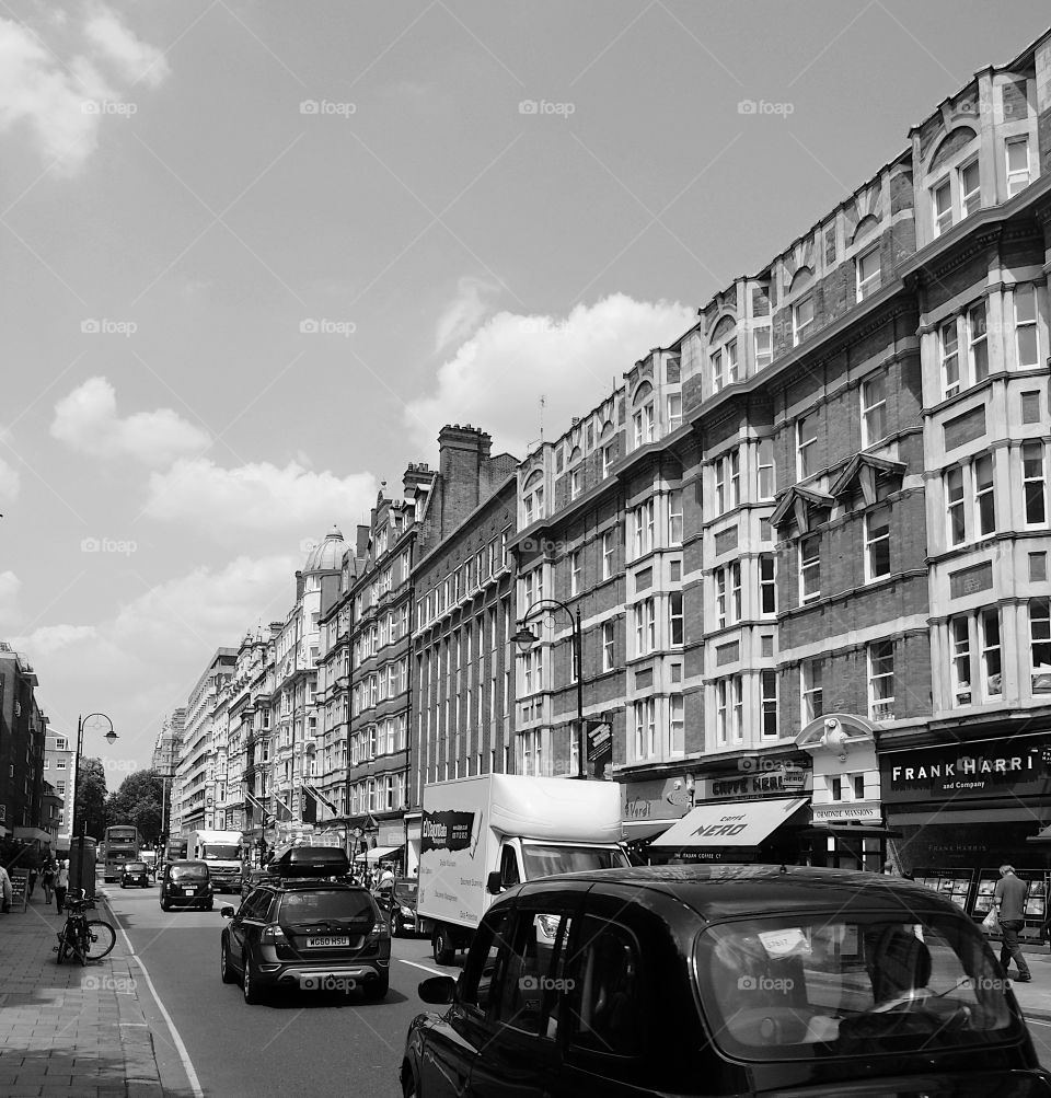 People walking and vehicles moving and parked on a busy ornate building lined buildings with shops on a busy street in London on a sunny summer day.