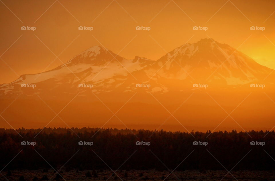 A very rare orange atmospheric glow over the Three Sisters in the Cascade Mountain Range in Central Oregon near sunset after a heavy rainstorm.