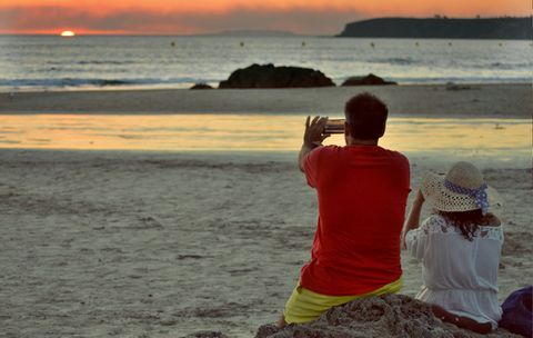 Rear view of couple taking photography of sunset at beach