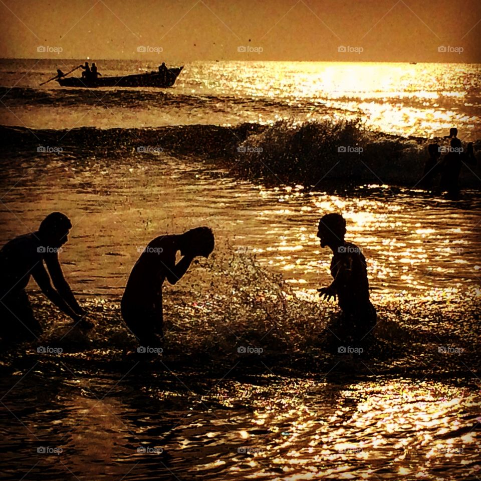 guys playing in beach silhouette