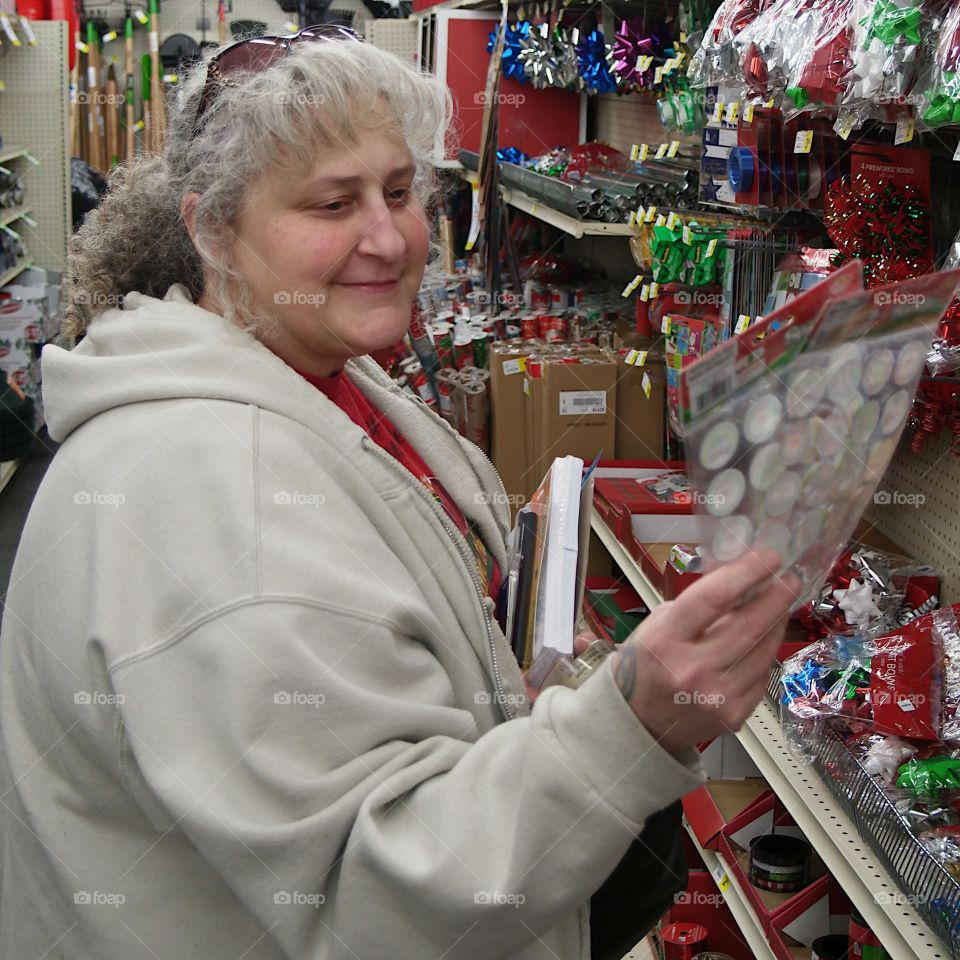 A woman views a package of stickers to use to decorate Christmas gift packages while shopping during the holiday season.