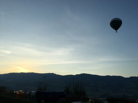 Hot air balloon over silhouetted mountain