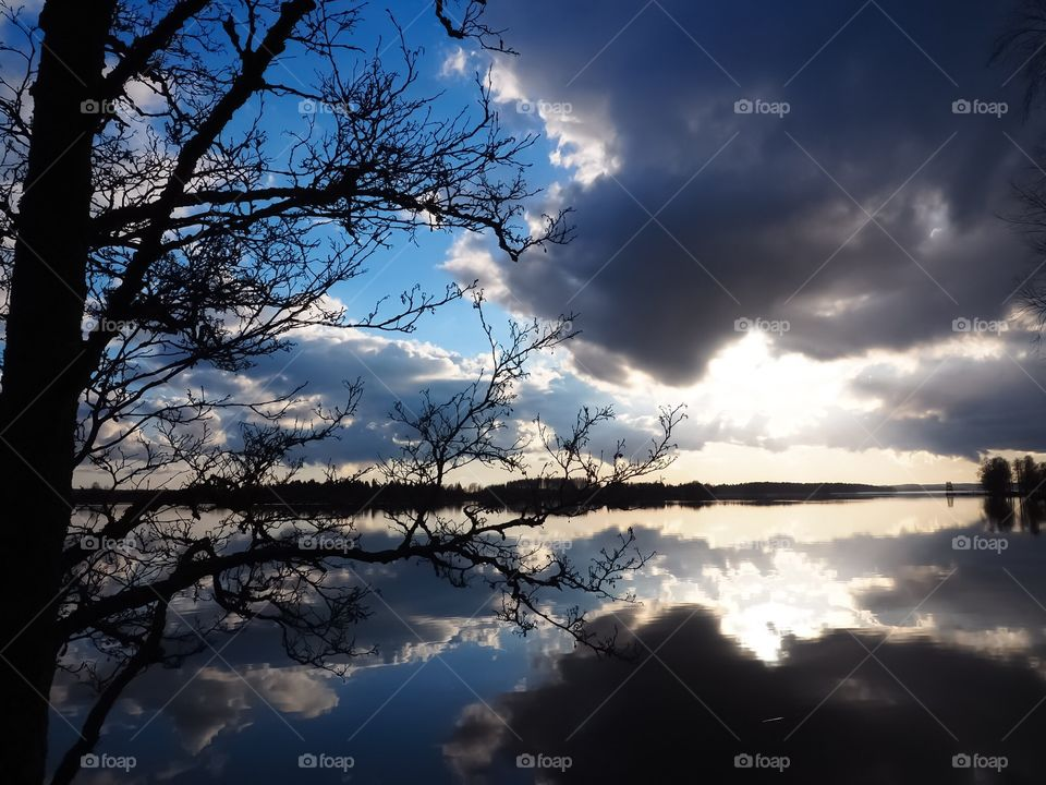 Cloudy sky is reflected on the surface of the water. Beautiful spring weather.