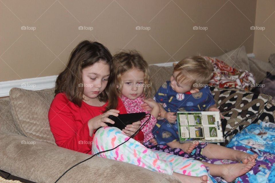 Cute little siblings sitting on couch