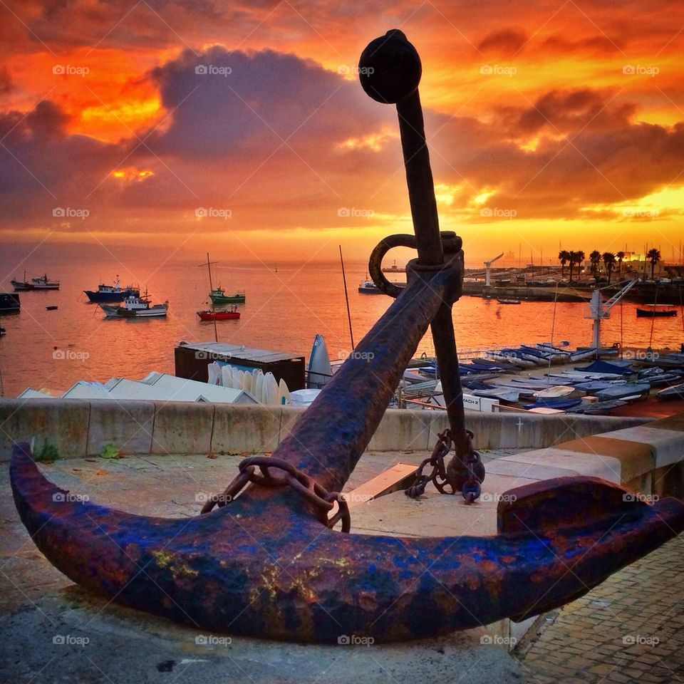 Rusty anchor at harbor during sunset