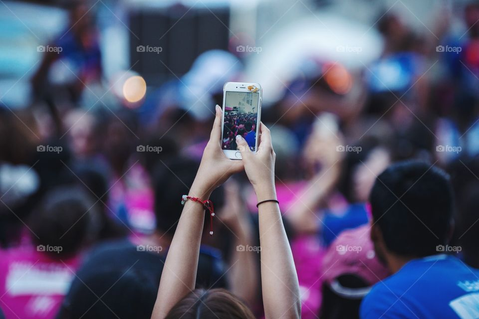 A young woman taking pictures on her phone