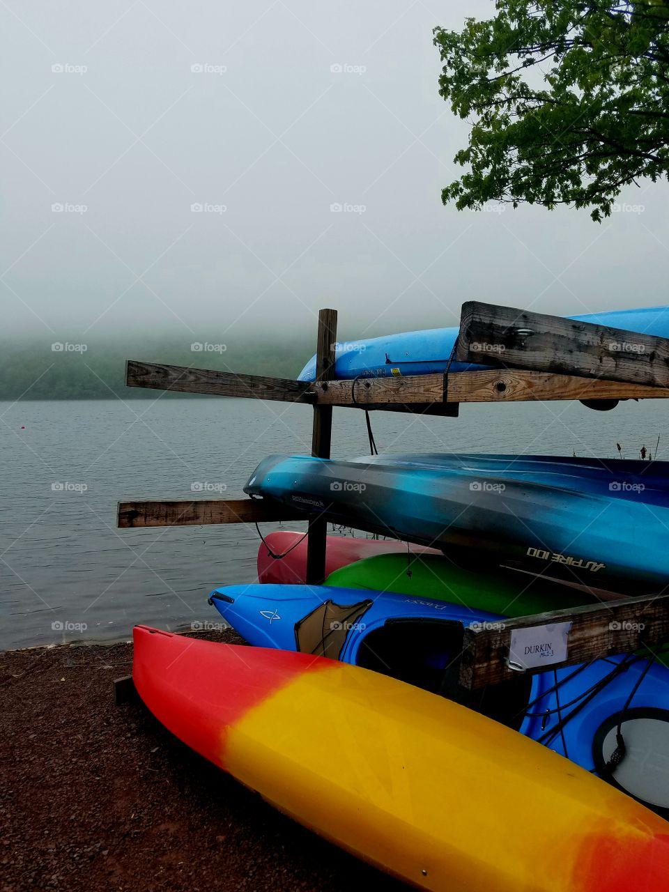 colorful rack of kayaks on foggy lake in morning
