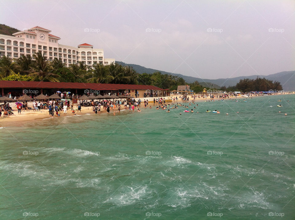 A view of the beach and vacationers having fun.