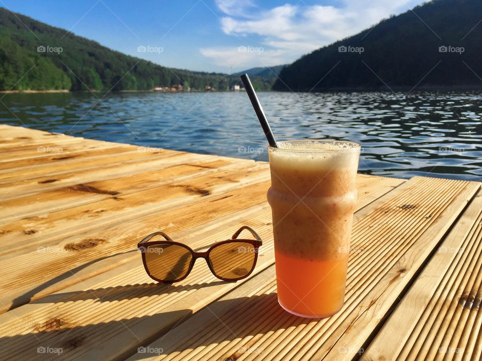 Glass of orange smoothie with drinking straw with a pair of sunglasses on a rustic wooden pontoon near the lake