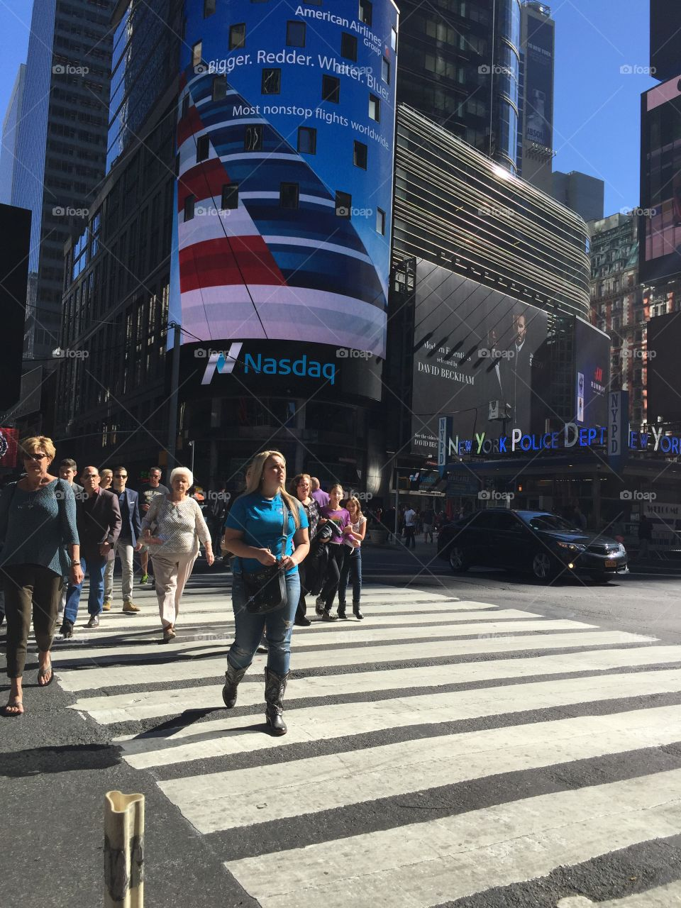 Pedestrians in crosswalk at Times Square New York City midtown Manhattan with Nasdaq and NYPD starion