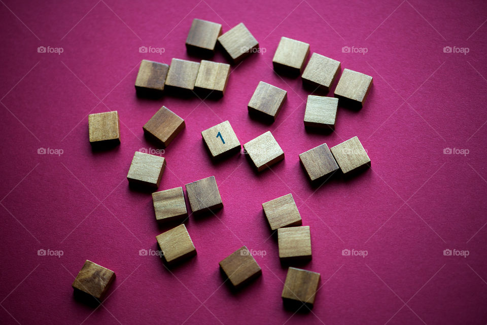 Wooden cube with the number one on purple background, top view