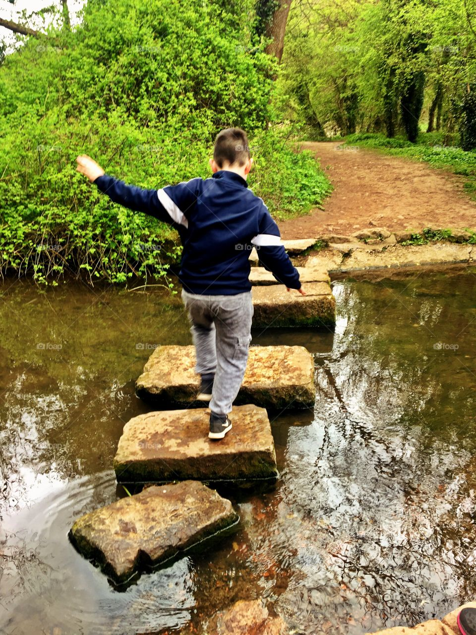 Boy crossing a river on stepping stones