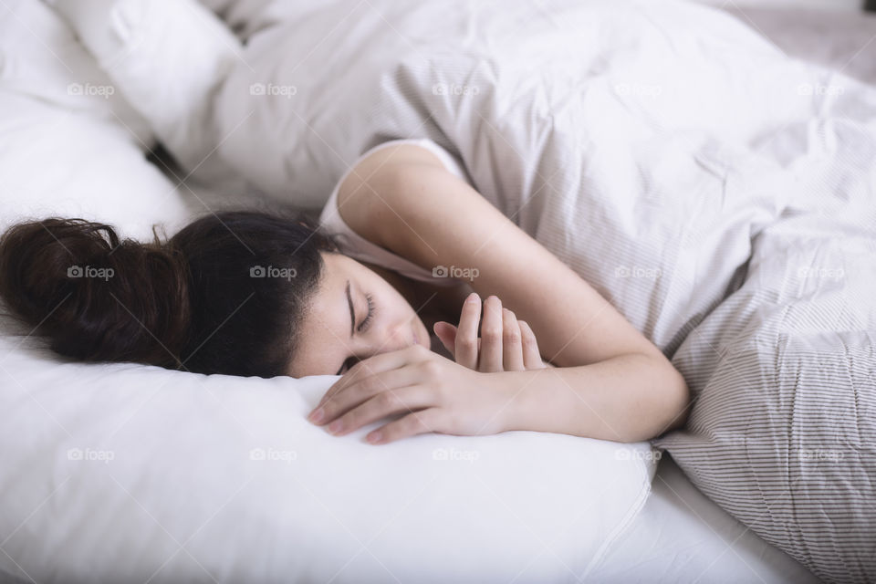 A lady sleeping under a white blanket