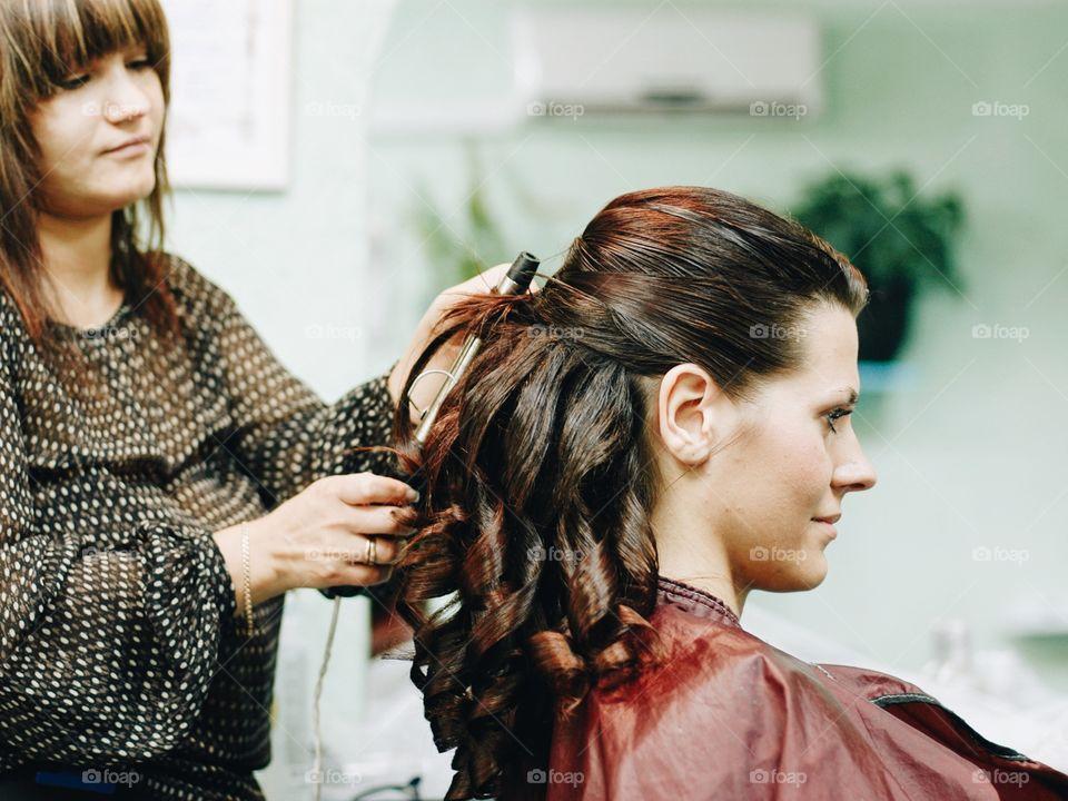 Female hairdresser works on woman hair in salon