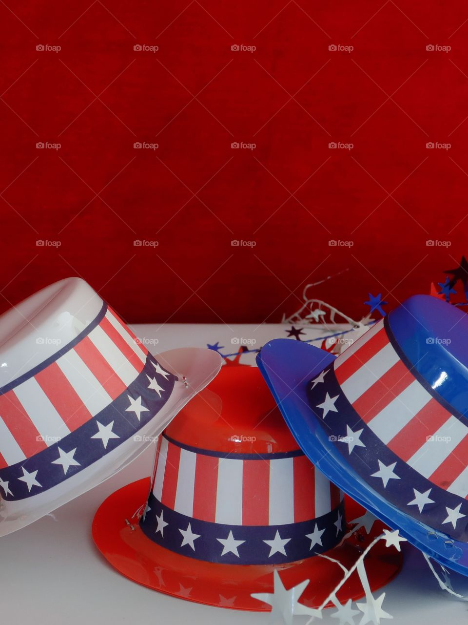 Tiny party hats in red, white, and blue with the Stars and Stripes for hat bands on a table with confetti.
