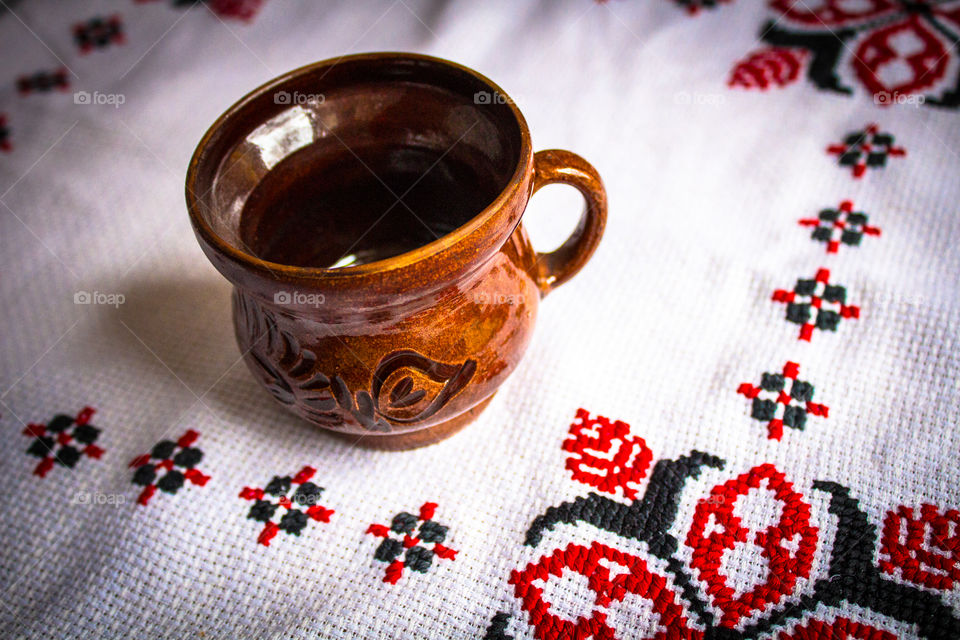 Beautiful traditional clay cup on a white traditional towel with red and black patterns stitching