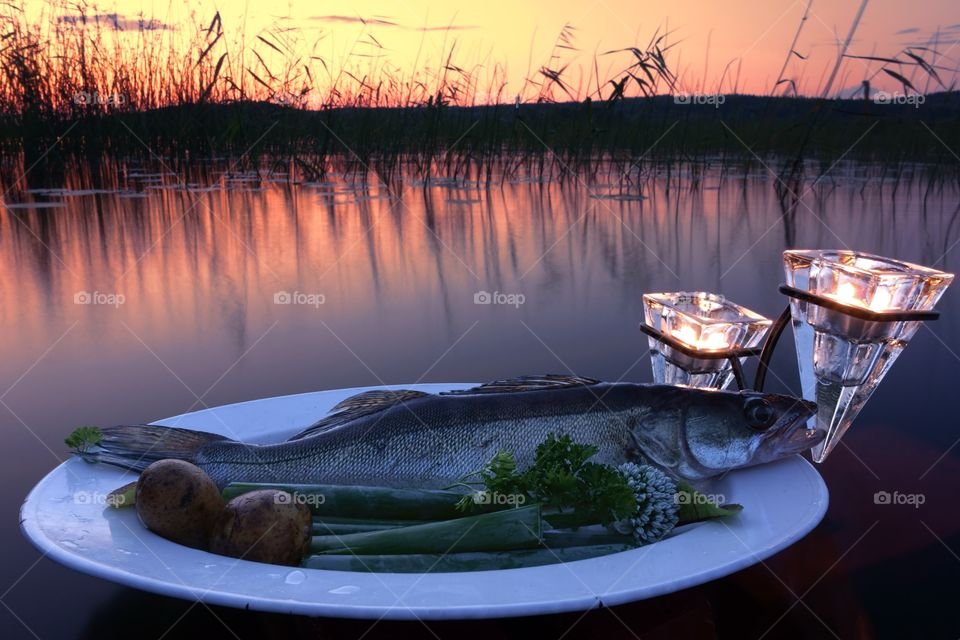 Fresh fish catch on a plate. Fresh fish catch (pike perch) on plate served with fresh vegetables in outdoors setting on a lake