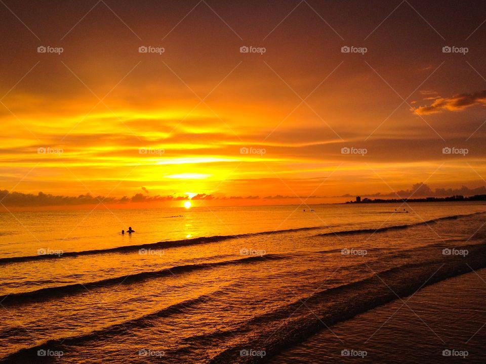 Sunset, swimmers, and waves. Sunset, swimmers, and waves