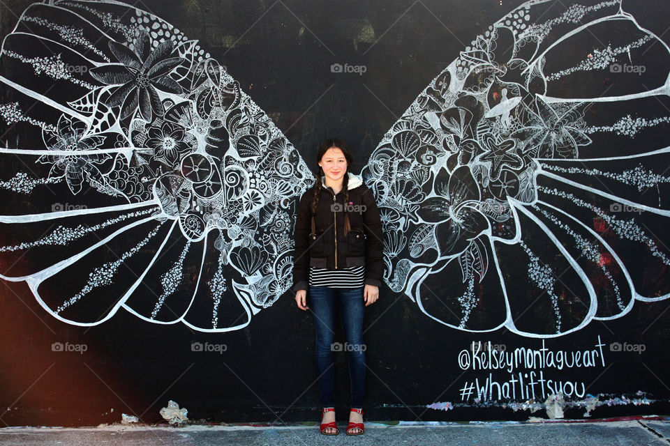 Young woman with wings on blackboard