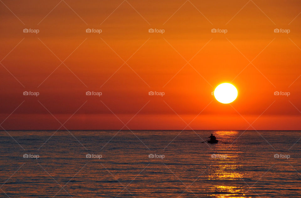 Silhouette of people boating in sea