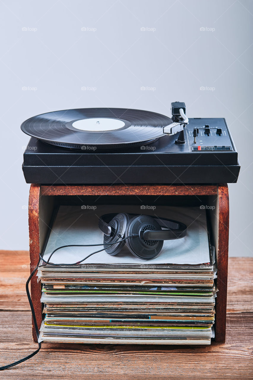 Stack of black vinyl records, turntable vinyl player and headphones. Classic stereo set. Candid people, real moments, authentic situations