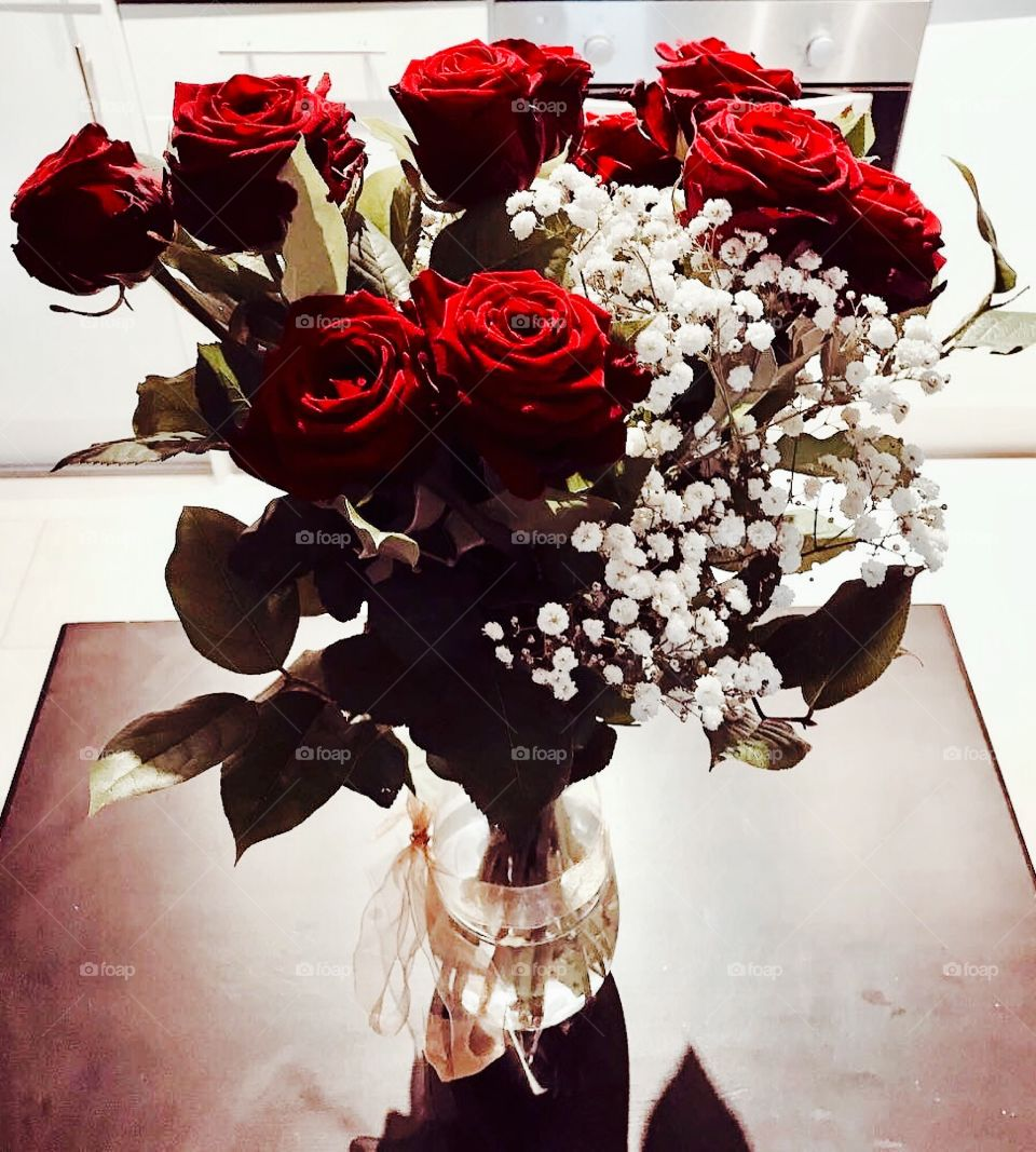 Colour contrast beautiful red roses, greenery and white blossom close up in a vase of water with a bow
