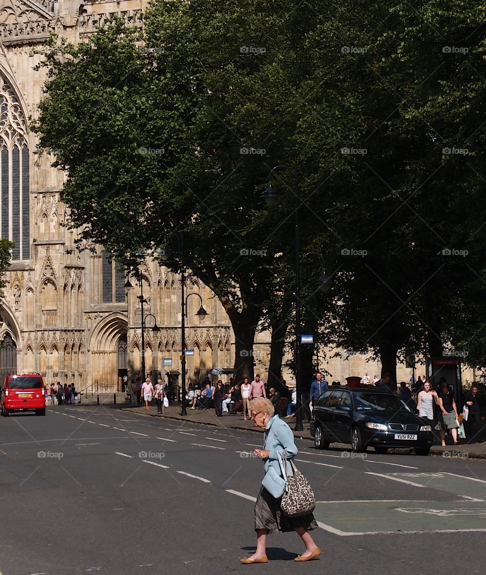A lady hurriedly crosses a street with a cathedral in the background on a sunny summer day in England.