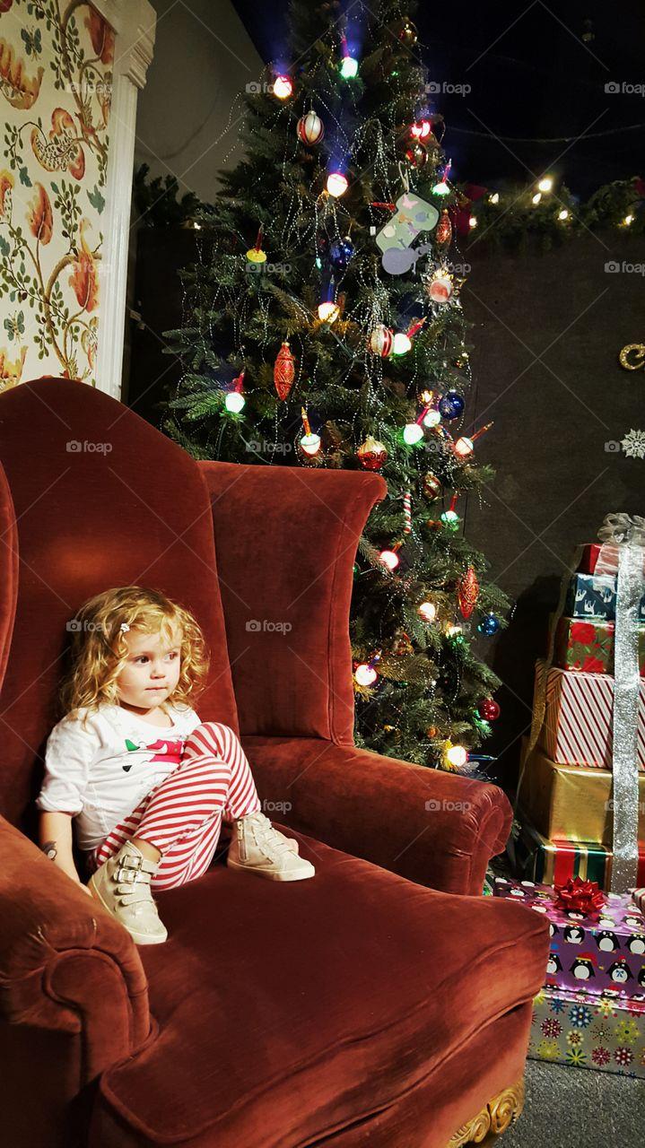 Girl sitting on chair near Christmas tree